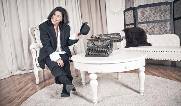 Maja Keaton stellt sich vor, sitzend auf Sessel und mit Melone und Schreibmaschine. Foto: Julie Fleur Photography